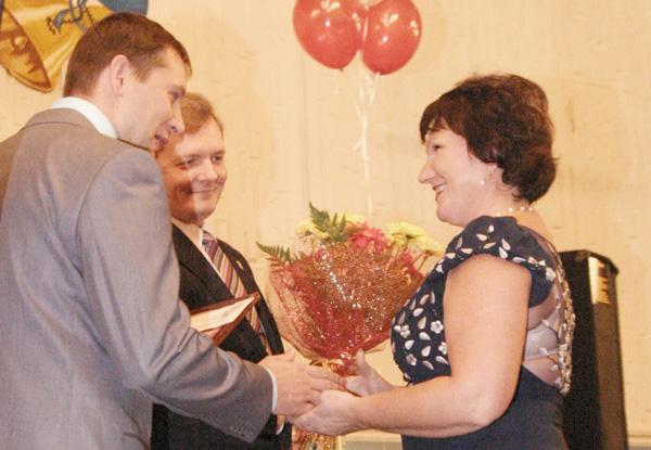 В. Гудок (слева) и Ю. Каршицкий вручают приз О. Лукашевой