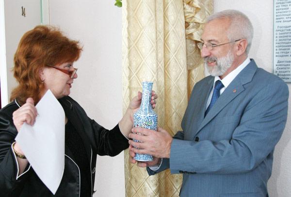 М. Крышнева передает Д. Несанелису вазочку, сделанную детскими руками