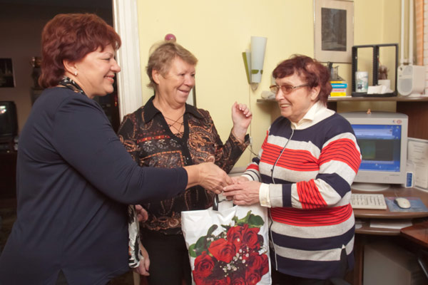 (слева направо) Е. Осмоловская и Н. Сахарова вручают подарки ветерану «ПечорНИПИнефти» Л. Поповой (Ухта)