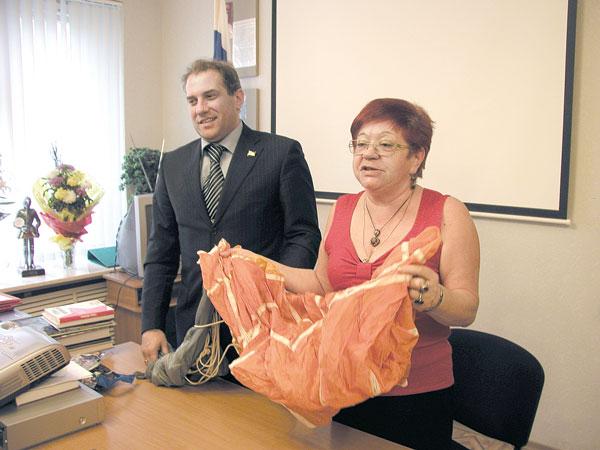 Н. Кулябов передает свой парашют руководителю музея боевой и трудовой славы Е. Холоповой