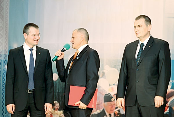 (слева направо) А. Щербина, глава МОГО «Ухта» – председатель Совета МОГО «Ухта» Р. Мельник и В. Гуляев поздравляют жителей Яреги со сцены