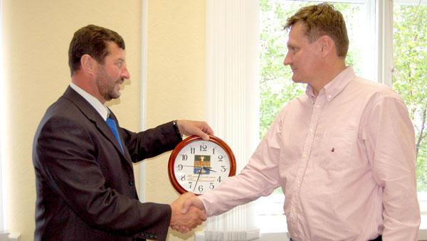 А. Чупров (слева) вручает Д. Астафьеву часы с логотипом Усть-Цильмы